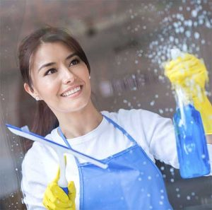 lady cleaning window with cleaning spray